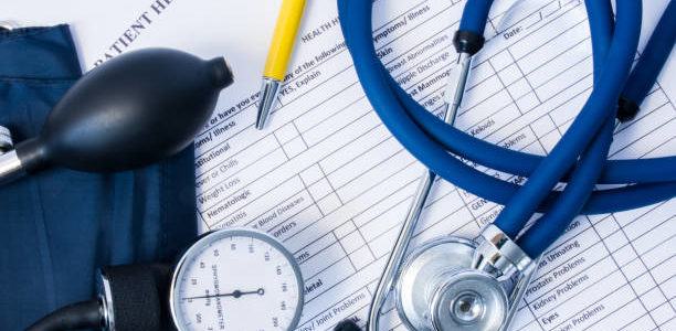 Diagnostic equipment - stethoscope, blood pressure gauge lying on patient health history and questionnaire of symptoms and the presence of previous disease. Scene with patient's physician consultation